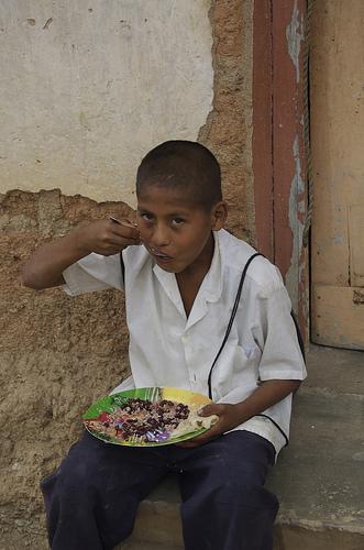 little boy eating beans